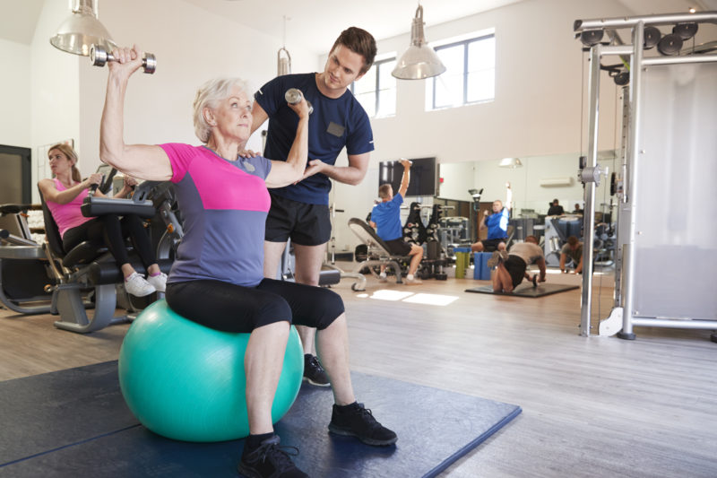 Senior Woman Exercising On Swiss Ball With Weights Being Encouraged By Personal Trainer In Gym